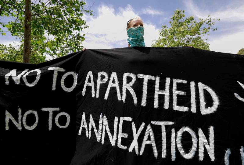 """TOPSHOT - An Israeli activist holds a banner during a protest against the US peace plan for the Middle East, in front of the US ambassador's residence in Jerusalem, on May 15, 2020, as Palestinians commemorate the 72nd anniversary of the 1948 Nakba or """"catastroph""""  which left hundreds of thousands of Palestinians displaced by the war accompanying the birth of Israel. The US plan, rejected by the Palestinians, gives the green light from Washington for Israel to annex Jewish settlements and other territory in the occupied West Bank.  / AFP / Emmanuel DUNAND"""