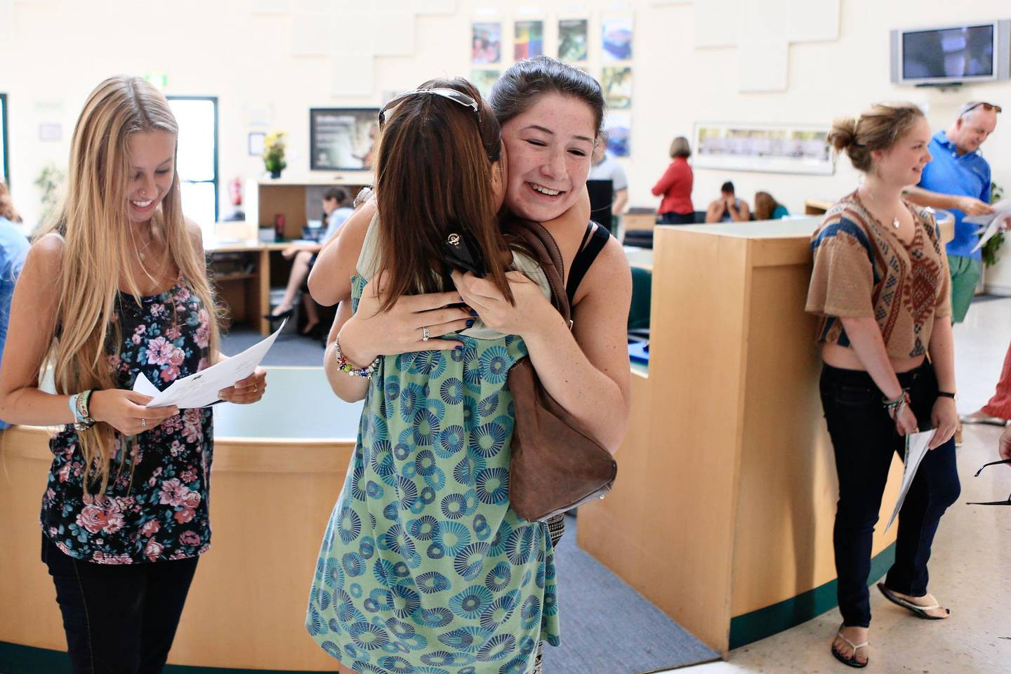 Dubai, August 15, 2013 -  (L to R) Emma Langley checks her year 13 A level results as her mother, Nicky Langley, embraces her classmate, Alice Taylor at Jumeirah College in Dubai, August 15, 2013. (Photo by: Sarah Dea/The National, Story by: Caline Malek) *** Local Caption ***  SDEA150813-A-Levels_Dubai03.JPG