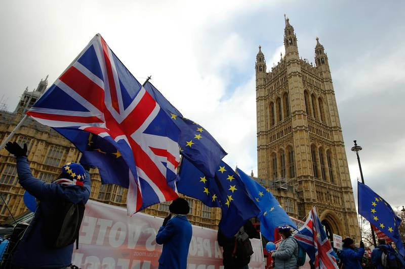 Anti-Brexit demonstrators wave European Union (EU) flags and British Union flags, also known as a Union Jacks, outside the Houses of Parliament in London, U.K., on Wednesday, Jan. 9, 2019. Mayresumes her bid to win Parliament's support for her Brexit deal, a day after lawmakers voted to make it harder for the U.K. to crash out of the European Union without an agreement. Photographer: Luke MacGregor/Bloomberg