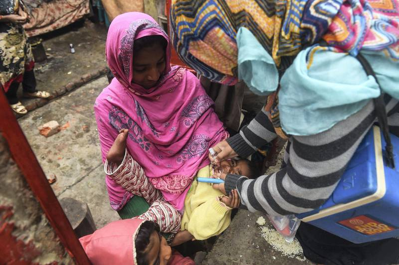 A Pakistani health worker administers polio vaccine drops to a child during a polio vaccination campaign at a slum area in Lahore on January 22, 2019. (Photo by ARIF ALI / AFP)