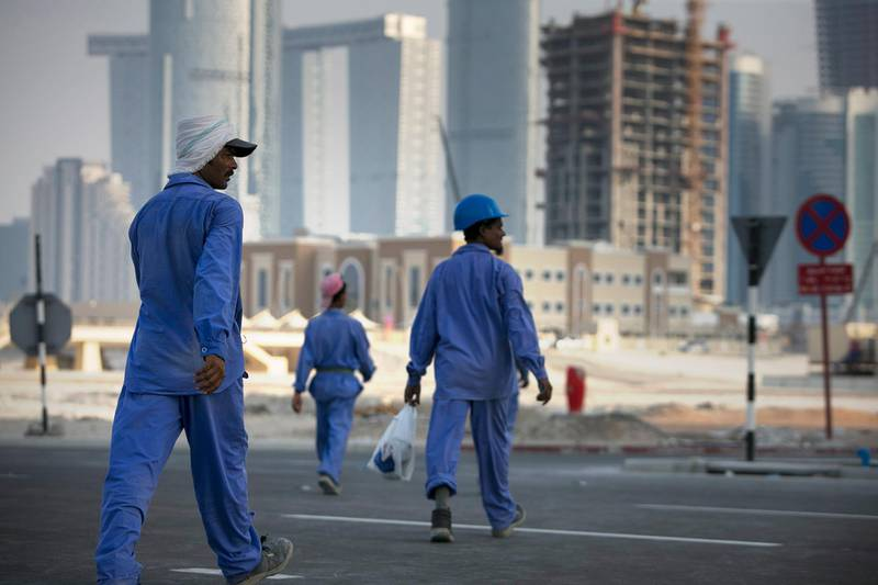 Abu Dhabi, UNITED ARAB EMIRATES, June 22, 2014:   Laborers rush toward their bus at the end of their shift, near new construction projects on Reem Island in Abu Dhabi as seen on Sunday, June 22, 2014. (Silvia Razgova / The National)  Reporter: standalone  Section: NA, BIZ Usage: stock