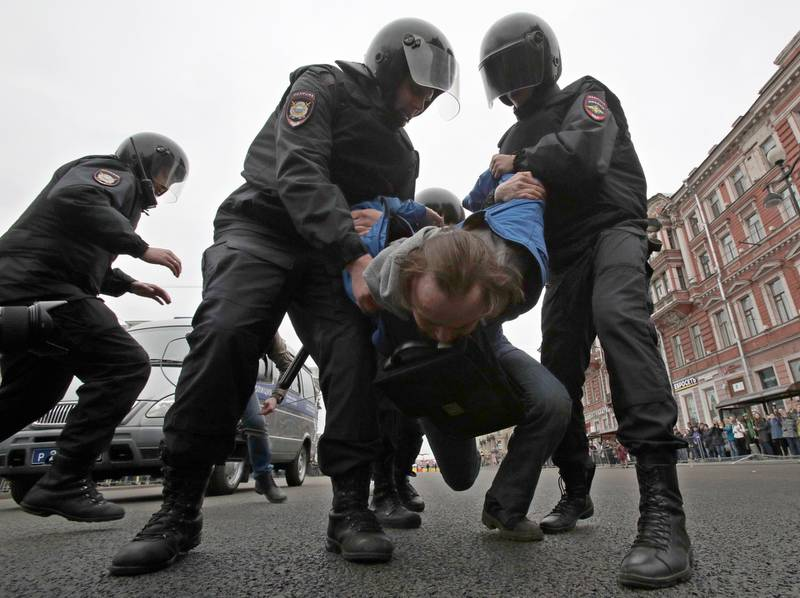Russian police detain a protester at a demonstration against President Vladimir Putin in St.Petersburg, Russia, Saturday, May 5, 2018. A group that monitors political repression in Russia says more than 350 people have been arrested in a day of nationwide protests against the upcoming inauguration of Vladimir Putin for a new six-year term as president. (AP Photo/Dmitri Lovetsky)