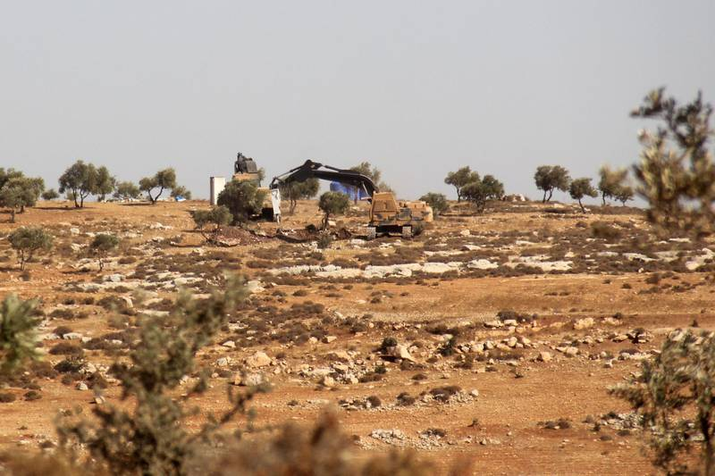 """A picture taken on October 14, 2017, shows Turkish army diggers on a hill in the Syrian border town of Salwah. Turkish forces have entered northwest Syria's largely jihadist-controlled Idlib province, observers said, where Ankara said this week it planned to create a """"de-escalation zone"""" as part of efforts to end the Syrian war. / AFP PHOTO / Omar haj kadour"""