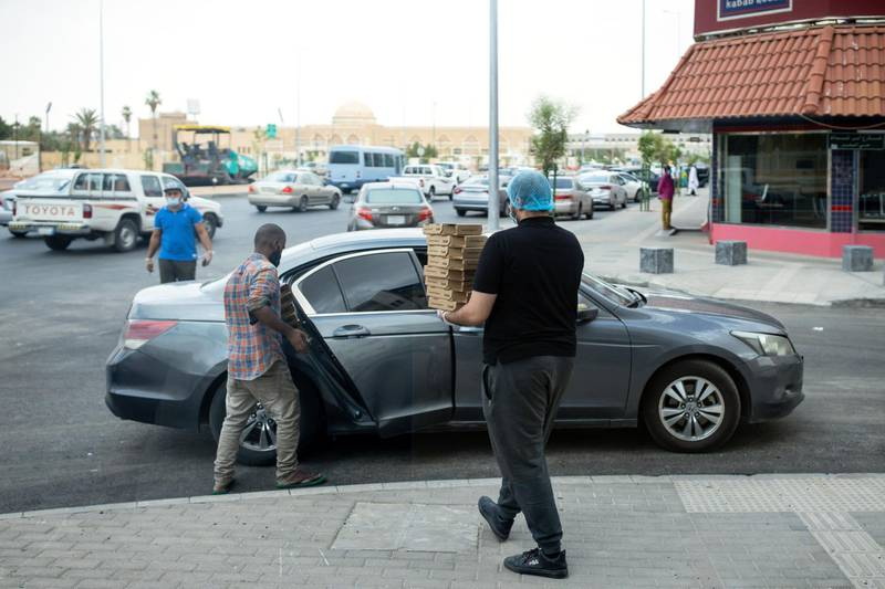 An employee carries pizzas in boxes for delivery to customers outside a Maestro Pizza food store in Riyadh, Saudi Arabia, on Tuesday, May 19, 2020. Hit simultaneously by plunging crude prices and coronavirus shutdowns, the non-oil economy is expected to contract for the first time in over 30 years. Photographer: Tasneem Alsultan/Bloomberg