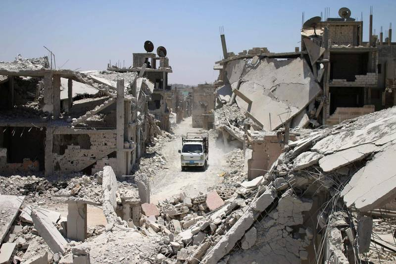 A teuck drives down a destroyed street in a rebel-held area in Daraa on July 19, 2017, as civilians started to return to the area following the July 9 agreement ceasefire brokered by the United States, Russia and Jordan creating a de-escalation zone in Syria's southern Daraa, Quneitra and Sweida regions.  / AFP PHOTO / Mohamad ABAZEED