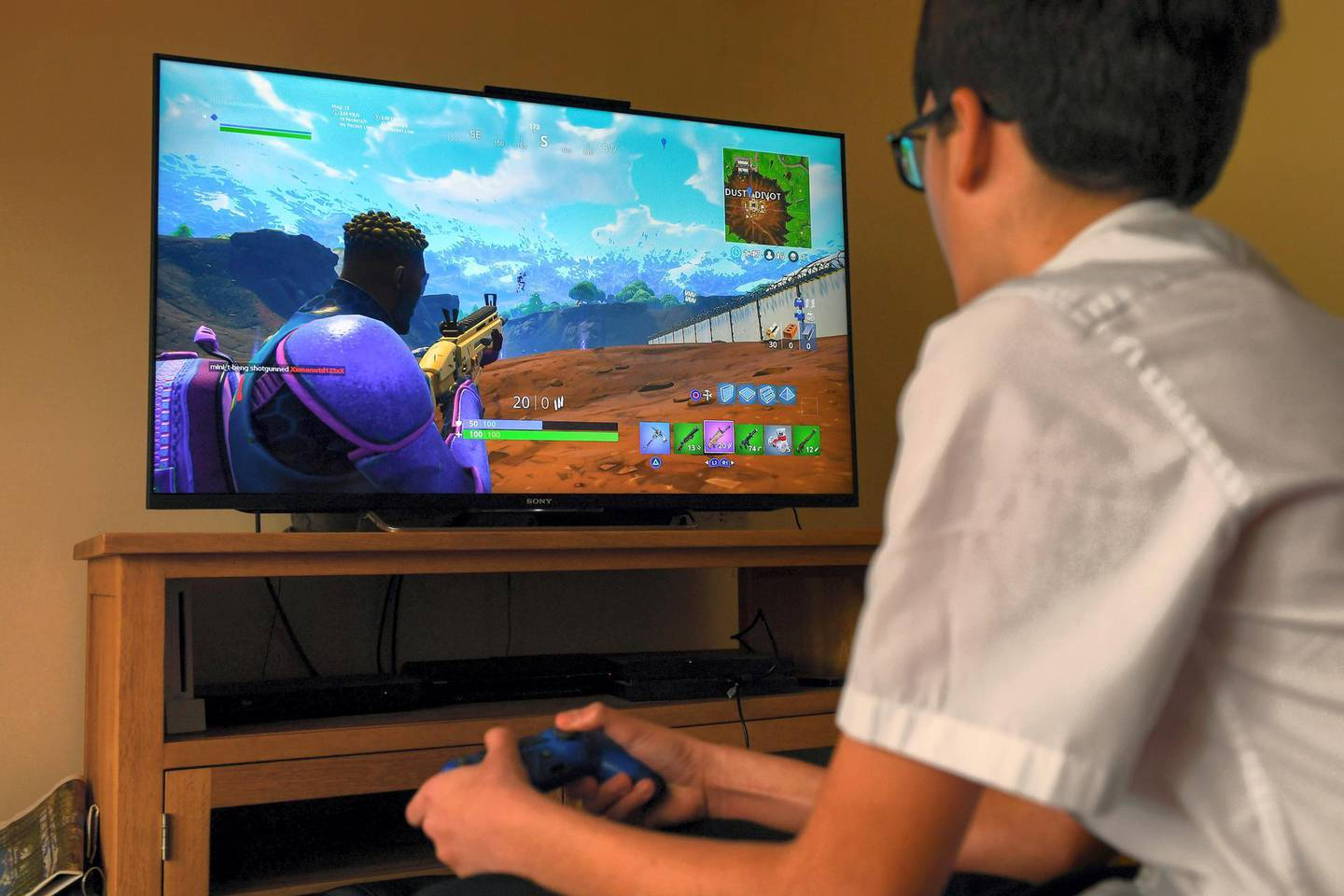 MHN53F A teenager boy plays the hit computer game Fortnite on a large TV on a Playstation 4 console.