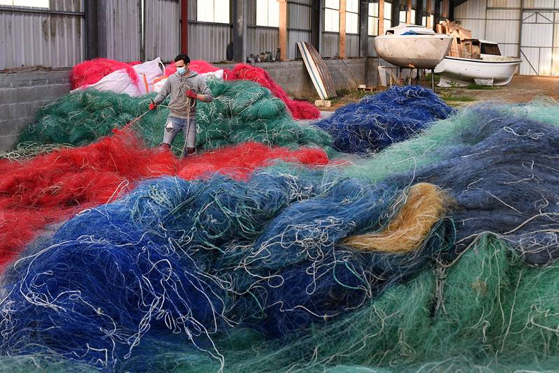 A worker sorts out used nylon fishnets at the warehouse of the Fil & Fab company, specialized in the recycling and sale of plastic from nylon fishing nets, in Plougonvelin, western France on November 12, 2020. - The company Fil&Fab, created in 2019 in the Bretagne region by three young designers, weaves its fabric with the aim of eventually launching objects that are 100% made from recycled fishing nets. (Photo by Fred TANNEAU / AFP)