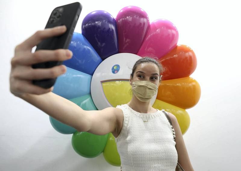 Dubai, United Arab Emirates - Reporter: Alexandra Chaves. Arts and Lifestyle. A visitor takes a picture in the Perrotin section with a piece of artwork by Takashi Murakami. Art Dubai 2021 opens at the DIFC. Tuesday, March 30th, 2021. Dubai. Chris Whiteoak / The National