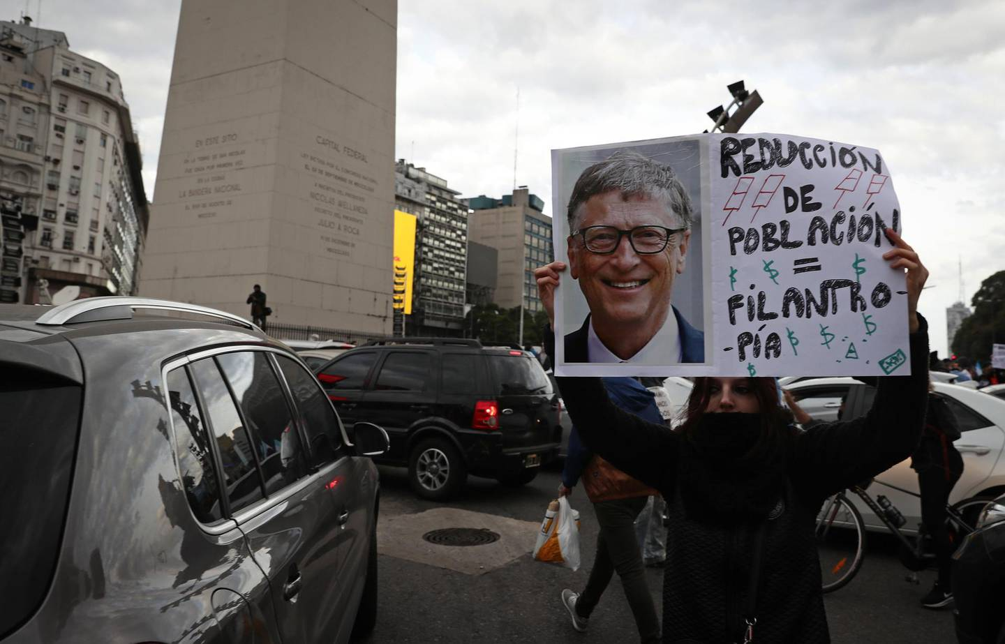 A woman holds a sing with the image of the Co-chair and Trustee of the Bill and Melinda Gates Foundation, Bill Gates, during a demonstration called by small businessmen affected by the government's mandatory quarantine imposed for more than 13 weeks, to protest against the quarantine and the expropriation of the Vicentin agro-industrial company on the Obelisk in Buenos Aires, June 20, 2020. Argentine President Alberto Fernandez announced on June 8 the nationalisation of soy giant Vicentin, which was the country's largest grain exporter until it entered a crisis at the end of last year. / AFP / ALEJANDRO PAGNI