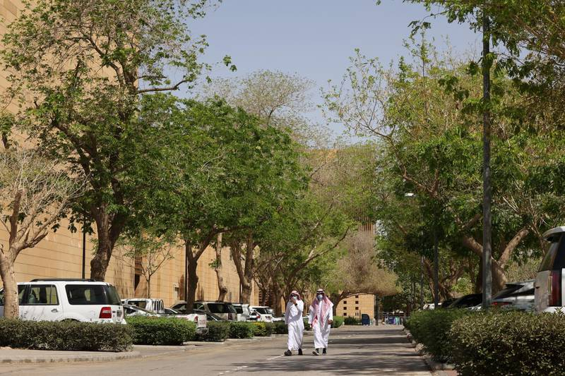 """People walk on a tree-lined lane in the Saudi capital Riyadh, on March 29, 2021. - Although the OPEC kingpin seems an unlikely champion of clean energy, the """"Saudi Green Initiative"""" aims to reduce emissions by generating half of its energy from renewables by 2030. (Photo by Fayez Nureldine / AFP)"""