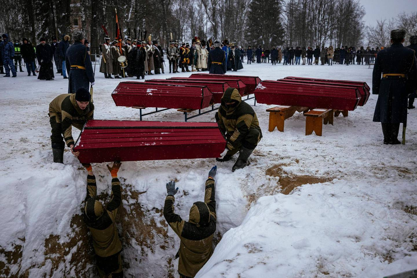 Municipal employees hold a coffin containing remains of Russian and French soldiers during a burial ceremony in the western town of Vyazma on February 13, 2021. Officials and descendants of 19th-century Russian and French military leaders gathered for a windswept ceremony in the western town of Vyazma to re-bury the remains of 126 people killed in one of the bloodiest battles of Napoleon's Russian campaign. / AFP / Dimitar DILKOFF