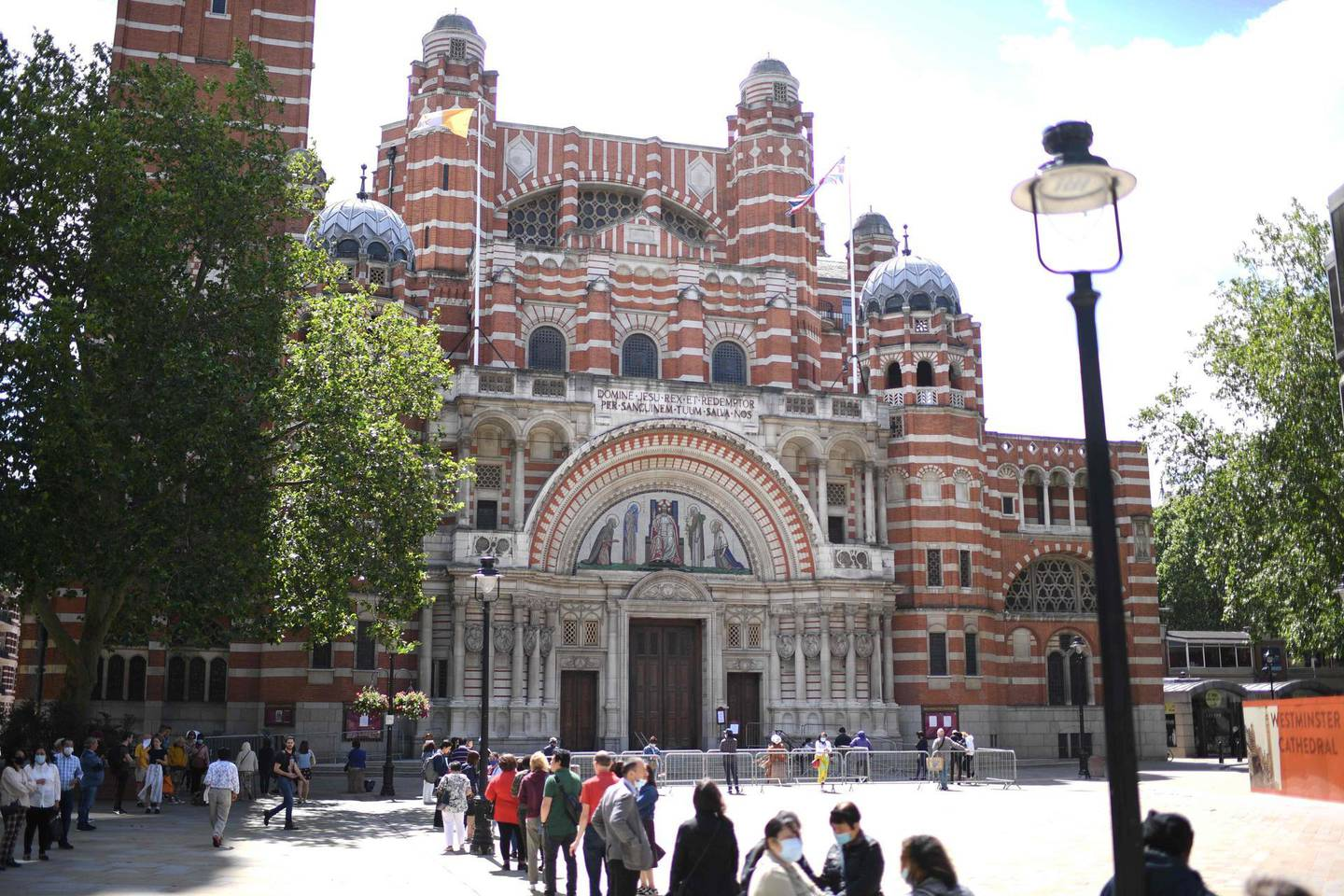 Worshippers queue to enter Westminster Cathedral in London on July 5, 2020 for Sunday Mass on the first Sunday since coronavirus lockdown restrictions were eased to allow for communal prayer.  The Christian devotee is a regular at Westminster Cathedral and has been attending services with her statue of Jesus sitting atop the globe for 26 years. Churches opened their doors for Sunday Mass for the first time in months since the coronavirus restrictions were eased in England.  / AFP / DANIEL LEAL-OLIVAS