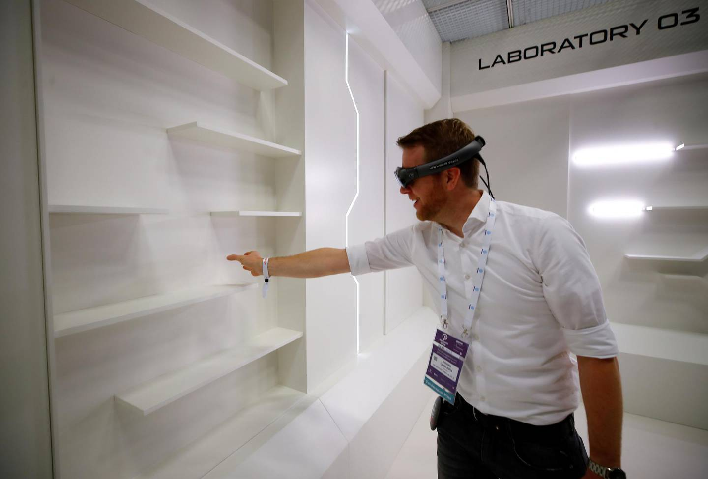 FILE PHOTO: A gamer grabs for a virtual book from an empty shelf as he wears augmented reality goggles during the media day of Europe's leading digital games fair Gamescom, which showcases the latest trends of the computer gaming scene, in Cologne, Germany, August 20, 2019. REUTERS/Wolfgang Rattay/File Photo