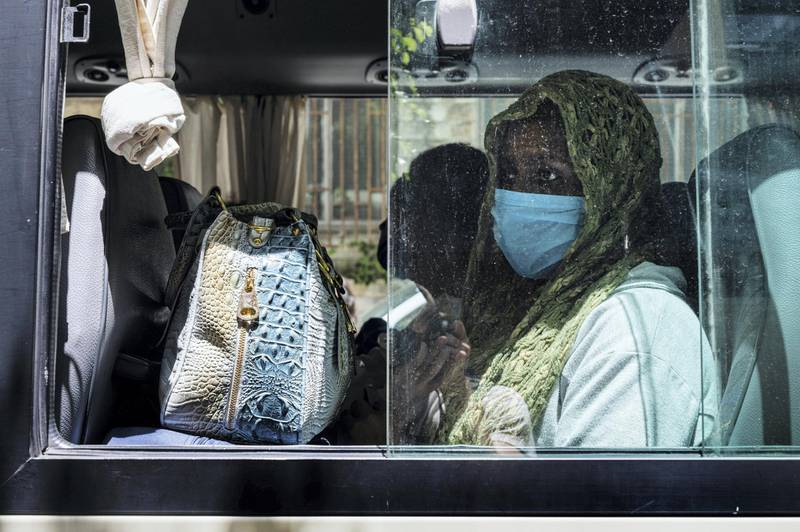 Women wait in the bus to be transported to shelters, where they will stay until Beirut's airport reopens. Finbar Anderson for The National
