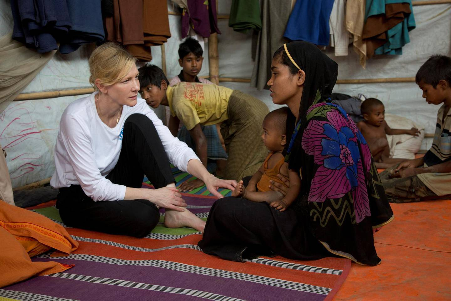 Cate Blanchett, Goodwill Ambassador for UNHCR, the UN Refugee Agency, speaks with Rohingya refugee Nur Fatima and her one-year-old son at the Nayapara refugee camp near Cox's Bazar, Bangladesh March 15, 2018. UNHCR/Hector Perez/Handout via REUTERS ATTENTION EDITORS - THIS IMAGE WAS PROVIDED BY A THIRD PARTY. MANDATORY CREDIT. NO RESALES. NO ARCHIVES. EDITORIAL USE ONLY IN REPORTING ON - UNHCR - WORLD REFUGEE DAY. NO NEW USE AFTER JULY  20, 2021.