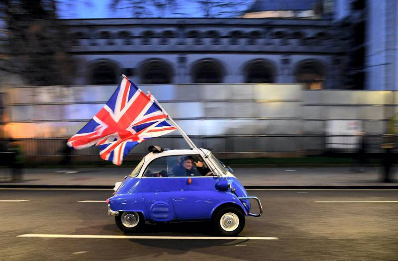 (FILES) In this file photo taken on January 31, 2020 a man waves Union flags from a BMW Isetta as he drives past Brexit supporters gathering in Parliament Square, in central London, on the day that the UK formally leaves the European Union. Five years on from Britain's shock decision to quit the European Union, the wounds opened by Brexit have yet to heal, and analysts say its far-reaching changes are only just beginning. / AFP / DANIEL LEAL-OLIVAS