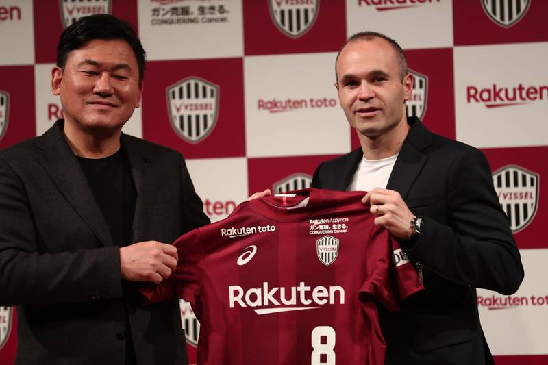 Spanish football star Andres Iniesta (R) and Hiroshi Mikitani, owner of Rakuten and Vissel Kobe club, hold the team's jersey during a press conference in Tokyo on May 24, 2018.  / AFP / Behrouz MEHRI