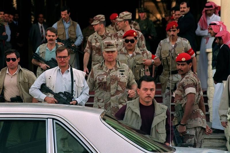 Gulf War commander, US four star general Norman Schwarzkopf (C), who commanded the international coalition which ousted Iraqi forces from Kuwait during Operation Desert Storm, leaves 10 February 1991 in Riyadh the Hotel Hayatt under the watchful eyes of his bodyguards. (Photo by MICHEL GANGNE / AFP)