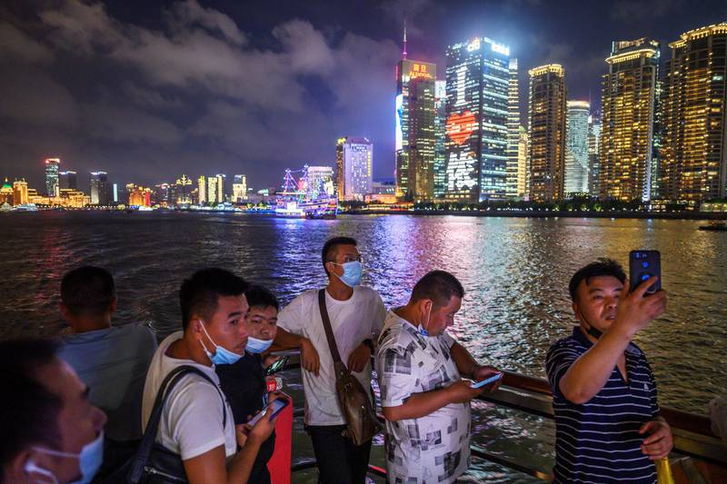 SHANGHAI, CHINA - SEPTEMBER 01: Chinese tourists, some wearing protective masks, take photos and stand on the deck of a tourist boat on the Huangpu River as the skyline of the Pudong district can be seen on September 1, 2020 in Shanghai, China. (Photo by Kevin Frayer/Getty Images)